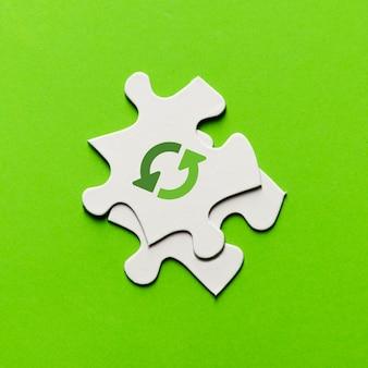 Vista elevada del icono de reciclaje en la pieza del rompecabezas blanco sobre fondo verde