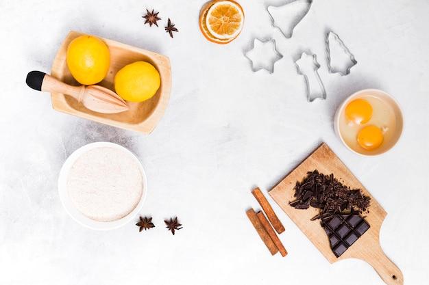 Una vista elevada de ingredientes y cortadores de pastelería sobre fondo blanco con textura