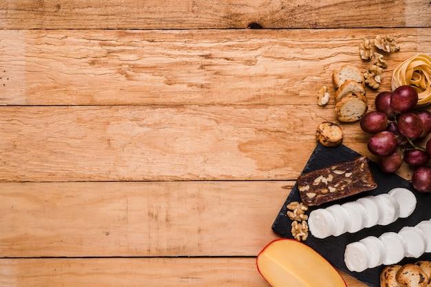 Vista elevada de ingredientes crudos saludables con queso en piedra de pizarra