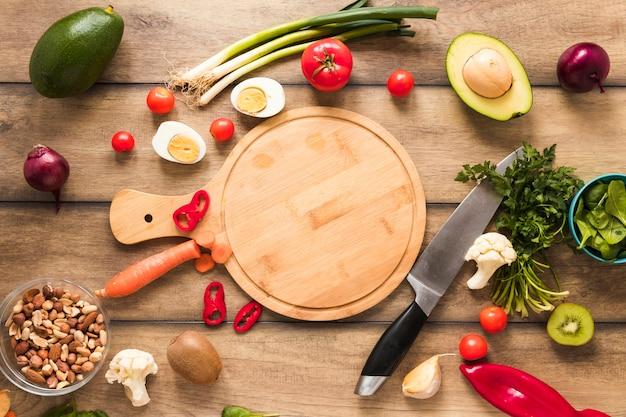 Vista elevada de ingredientes frescos; huevo; verduras y tabla de cortar con un cuchillo en la mesa