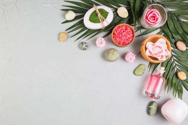 Vista elevada de jabón; piedras de spa; hojas; crema hidratante; aceite y flores en superficie gris.