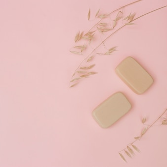 Vista elevada de jabones y cáscara sobre superficie rosada.