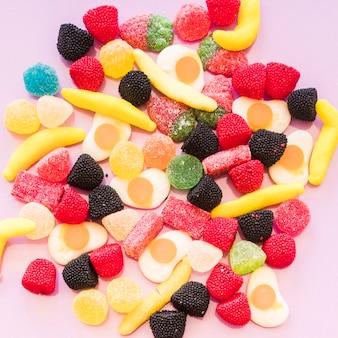 Vista elevada de jalea colorida y caramelos de azúcar gomosos sobre fondo rosa