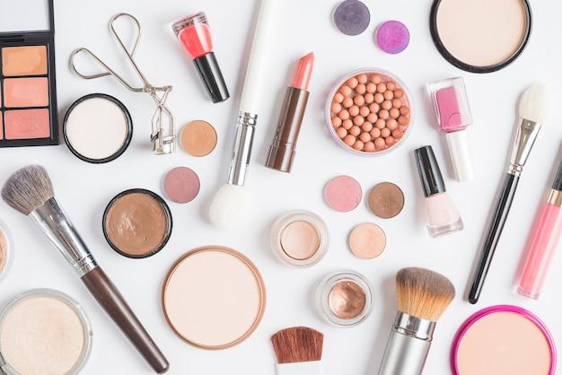 Vista elevada de kits de maquillaje sobre fondo blanco