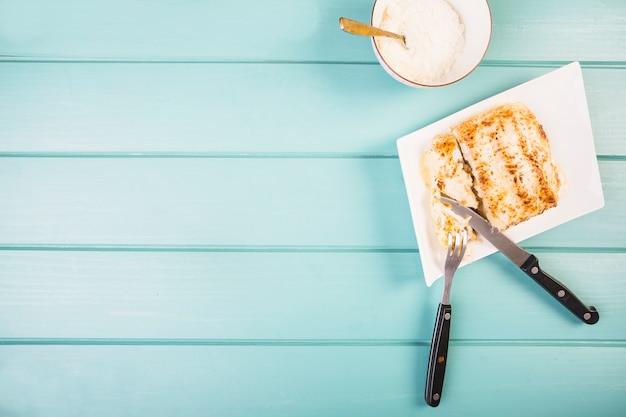 Vista elevada de lasaña con tenedor y cuchillo