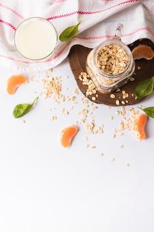 Una vista elevada de la leche; hojas de albahaca; avena; rodajas de naranja y servilleta sobre fondo blanco