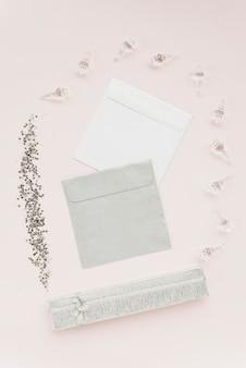 Vista elevada de lentejuelas; conchas de cristal; sobres y regalo sobre fondo de color.