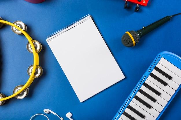 Vista elevada de la libreta espiral en blanco con auricular; guitarra; micrófono; teclado de piano y pandereta sobre fondo azul