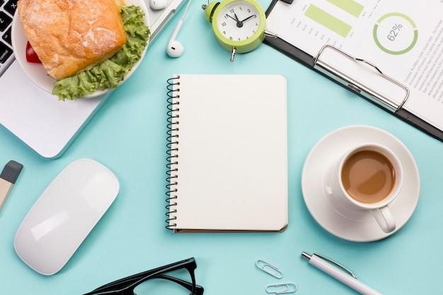 Una vista elevada de la libreta espiral, desayuno, mouse y computadora portátil en el escritorio de la oficina
