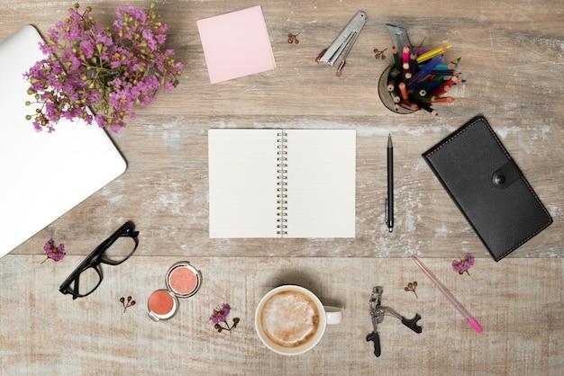 Vista elevada de un libro en blanco rodeado de suministros de oficina; productos de maquillaje; planta y laptop en mesa vieja