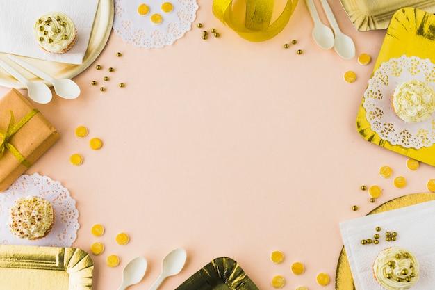 Vista elevada de magdalenas y regalos sobre fondo de color