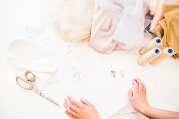 Vista elevada de la mano del diseñador con dibujo de moda y tela en el escritorio