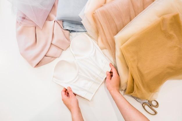 Vista elevada de la mano del diseñador de moda trabajando en telas en el estudio