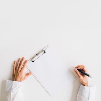 Vista elevada de la mano del doctor con papel blanco en blanco.