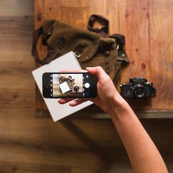 Vista elevada de la mano femenina tomando fotos de bolsa y cuaderno en la mesa