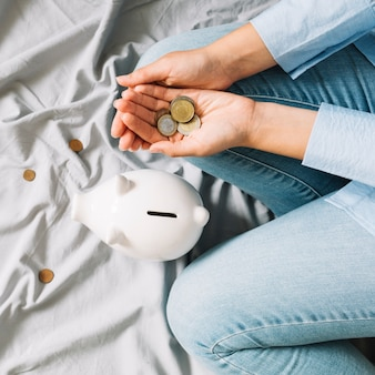 Vista elevada de la mano humana con monedas cerca de piggybank