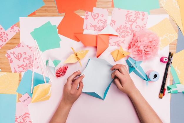 Vista elevada de la mano humana que hace el arte del papel del origami en la tabla de madera