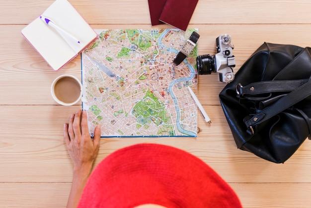 Vista elevada de la mano de la mujer con accesorios para el viajero y una taza de té en el escritorio