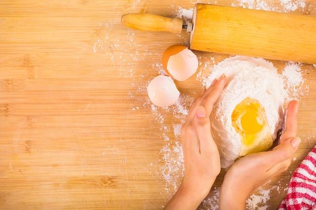 Vista elevada de la mano de mujer mezclando harina con huevo