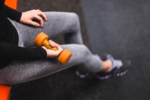 Vista elevada de la mano de una mujer que ejercita con pesa de gimnasia