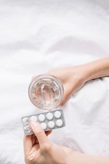 Vista elevada de la mano de la mujer con vaso de agua y pastillas