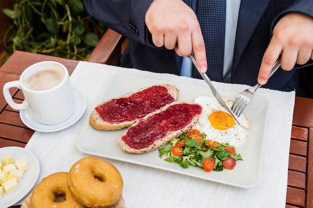 Vista elevada de la mano de una persona que come un desayuno saludable
