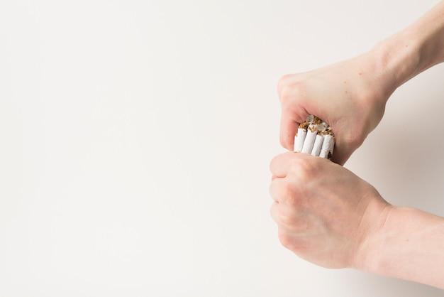 Vista elevada de la mano de una persona rompiendo cigarrillos sobre fondo blanco