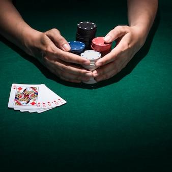 Vista elevada de una mano que paga póker en casino