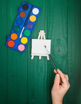 Vista elevada de la mano que sostiene el pincel sobre la mini paleta y la paleta de acuarela