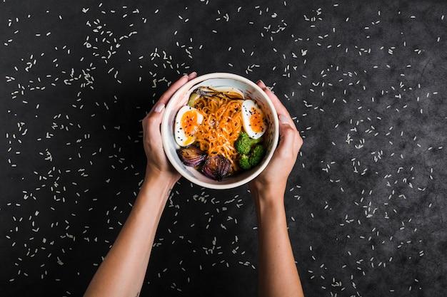 Una vista elevada de las manos que sostienen tazones de fideos ramen con huevos y ensalada con granos de arroz sobre fondo negro