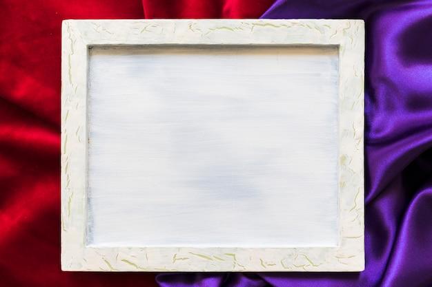Vista elevada del marco en blanco sobre textil rojo y púrpura.