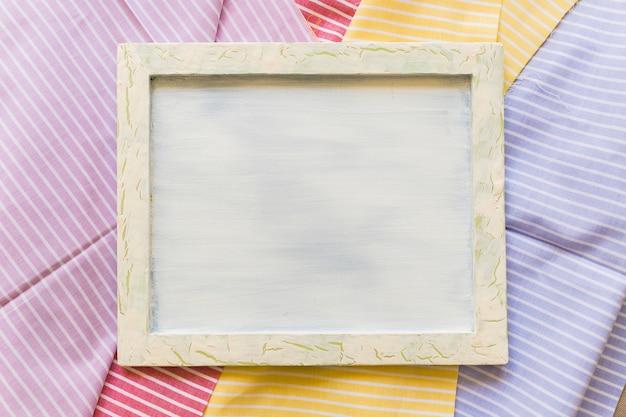 Vista elevada de un marco en blanco en textiles de patrones de rayas de colores
