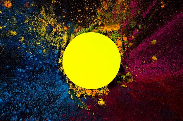 Vista elevada del marco circular amarillo cubierto con colores holi secos