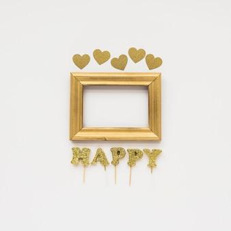 Vista elevada de marco dorado; texto feliz y forma de corazón en superficie blanca