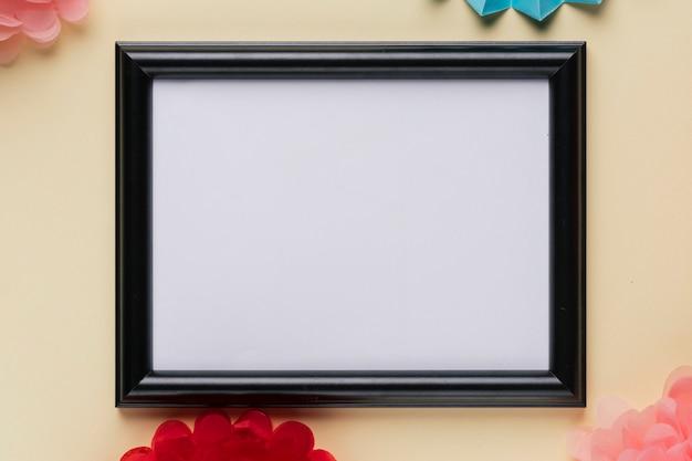 Vista elevada de marco vacío blanco sobre fondo beige