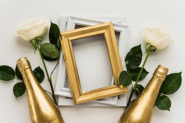 Vista elevada de los marcos de cuadros con dos rosas y una botella de champagne sobre una superficie blanca