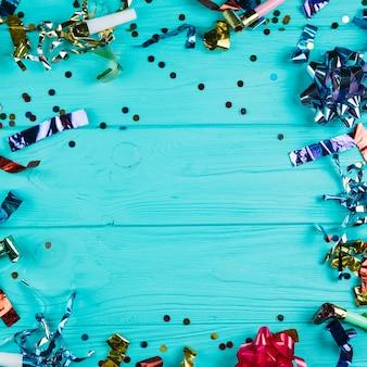 Vista elevada de material de decoración de fiesta brillante sobre escritorio azul