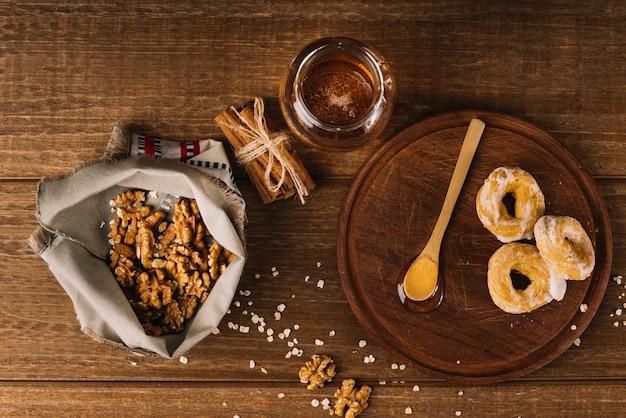 Vista elevada de la miel; nuez; especias y buñuelo en superficie de madera.