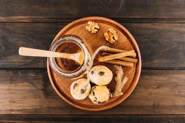 Vista elevada de la miel; nuez; especias y pasteles de taza sobre fondo de madera
