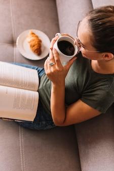 Una vista elevada de una mujer joven con un libro en su regazo tomando café