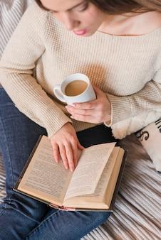 Una vista elevada de la mujer joven que sostiene la taza de café en el libro de lectura de la mano