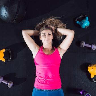 Vista elevada de una mujer joven tendida en el suelo rodeada de equipos de ejercicio