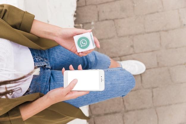 Vista elevada de una mujer sosteniendo el teléfono móvil y el bloque whatsapp