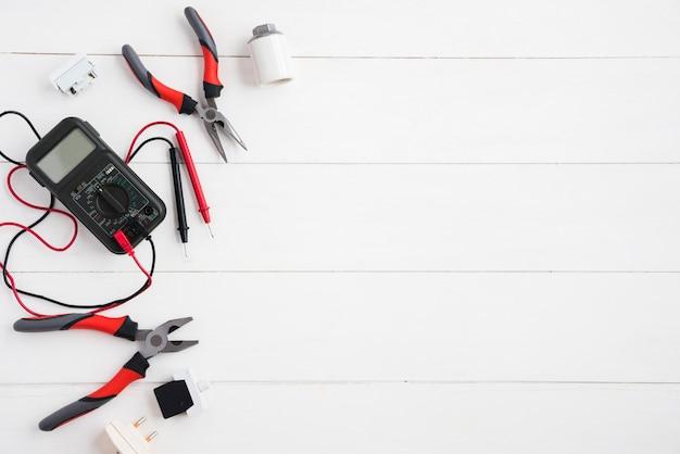 Vista elevada del multímetro digital y equipo eléctrico en el escritorio de madera blanco