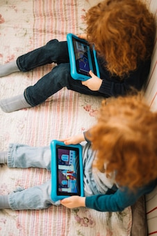 Una vista elevada de los niños viendo el video en una tableta digital.