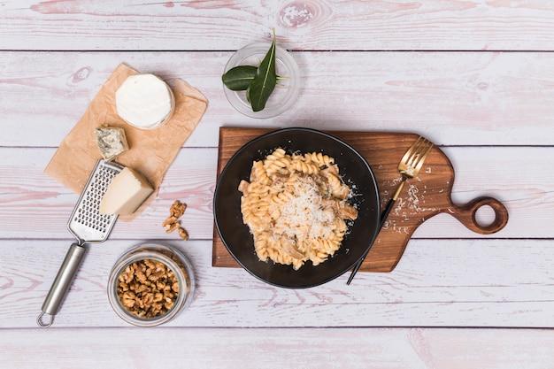 La vista elevada de nogal y la deliciosa pasta de fusilli trenzada adornan con queso rallado en superficie de madera