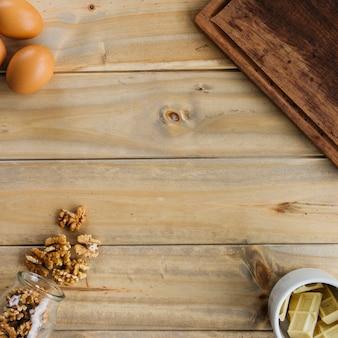 Vista elevada de nogal; trozos de chocolate y huevos marrones sobre fondo de madera