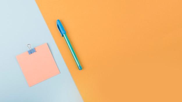 Vista elevada de la nota adhesiva y el bolígrafo sobre papel cartón colorido