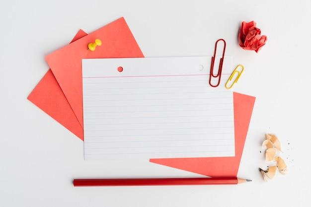 Vista elevada de notas adhesivas; lápiz; clip de papel y papel arrugado
