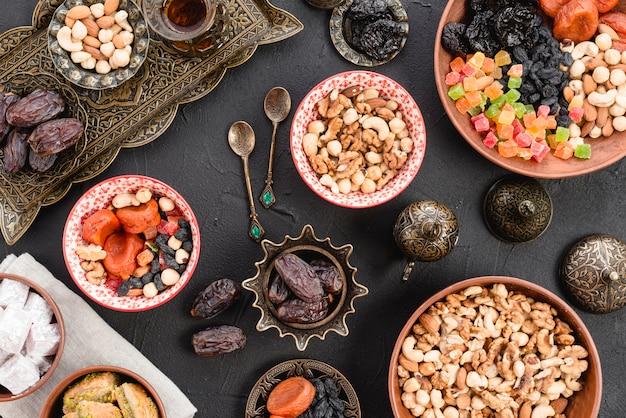 Una vista elevada de nueces; fechas; postre dulce en tazón de cerámica y metálico en mesa de concreto negro